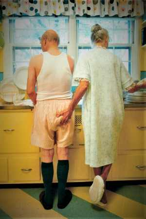 Older couple at kitchen sink. Woman in nightdress squeezing bottom of man wearing singlet and droopy shorts.